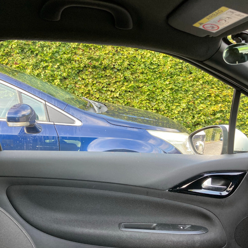 Door mirror aligned with front of parked car
